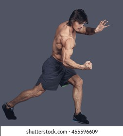 Shirtless muscular male in action isolated on a grey background.