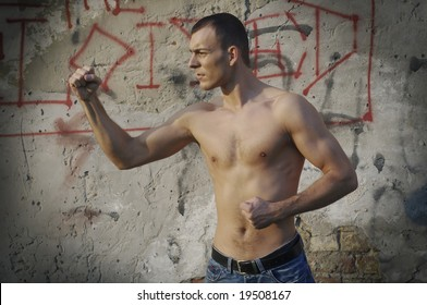 Shirtless muscular male model in front of the wall
