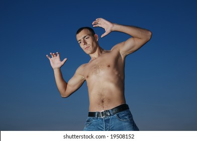 Shirtless muscular male model over evening sky