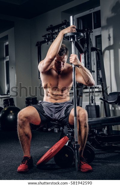 Shirtless muscular male training hard in a gym club.