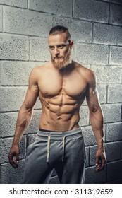 Shirtless muscular man with beard in grey pants posing over wall from grey bricks.