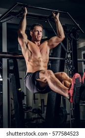 Shirtless muscular man doing ABS workouts on pull up bar in a gym.