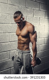 Shirtless muscular man doing biceps exercises with dumbbells.