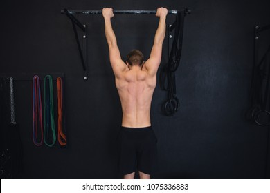 Shirtless muscular man is doing pull up in gym