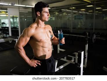 Shirtless muscular man holding energy drink in gym