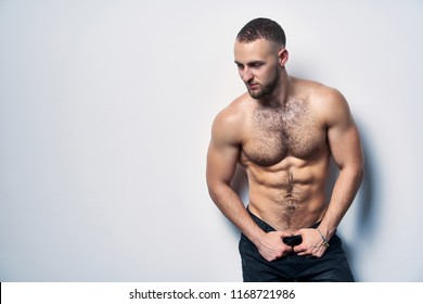 Shirtless muscular man in jeans standing at white wall posing looking down