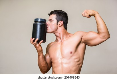 Shirtless muscular man kissing nutritional supplement over white background