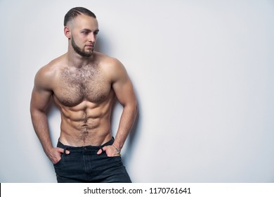 Shirtless muscular man standing by wall contemplating looking away