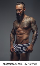 Shirtless muscular man with tattooes on his body. Isolated on a grey background.