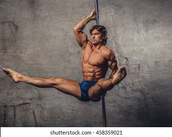 Shirtless muscular pole dancer in action.