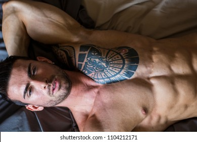 Shirtless muscular sexy male model lying alone on bed in his bedroom, looking away with a seductive attitude