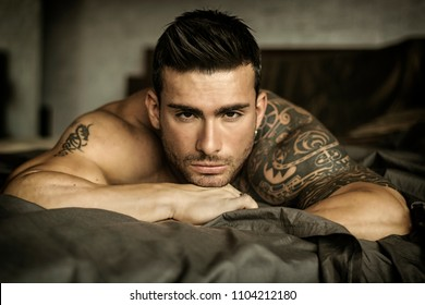 Shirtless muscular sexy male model lying alone on bed in his bedroom, looking at camera with a seductive attitude