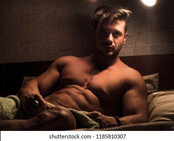 Shirtless muscular sexy male model lying alone on bed in his bedroom, relaxing