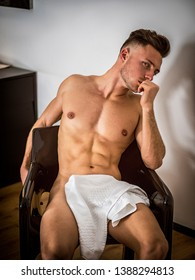 Shirtless naked sexy male model sitting alone on chair in his bedroom, looking at camera with a seductive attitude
