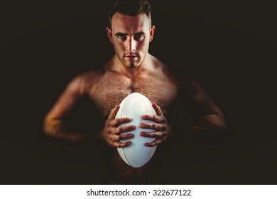 Shirtless rugby player holding ball on white background