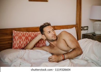 Shirtless sexy male model lying alone on his bed in his bedroom, looking away with a seductive attitude.Carefree guy enjoying new day.