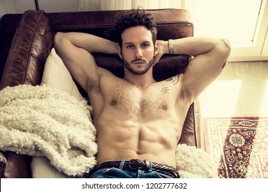 Shirtless sexy male model lying alone on couch in his living-room, looking at camera with a seductive attitude