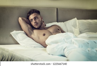 Shirtless sexy male model lying alone on his bed in his bedroom, looking around with a seductive attitude