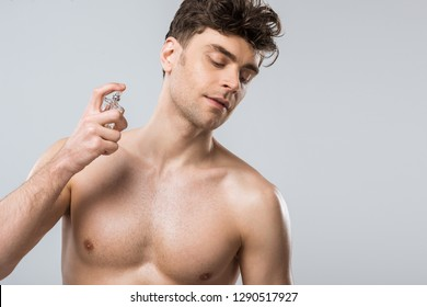 shirtless sexy young man spraying perfumes, isolated on grey