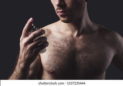 shirtless sexy young man spraying perfume