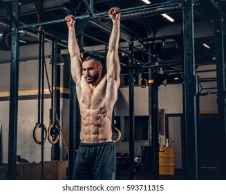 Shirtless sporty male doing ABS workouts on pull up bar in a gym club.