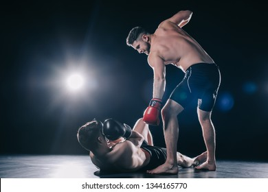 shirtless strong mma fighter in boxing gloves standing above opponent while sportsman lying on floor