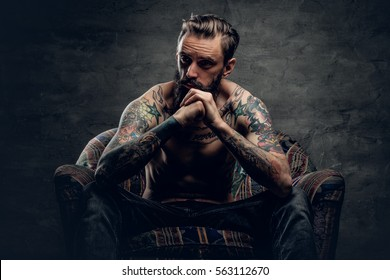 The shirtless, tattooed bearded male sits on a chair over grey background.