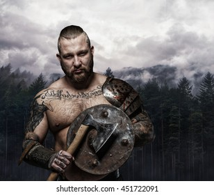 Shirtless tattooed viking holding wooden shield and axe over wild nature background.