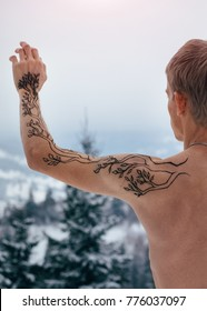 Shirtless well-built man shot from back with a raised hand covered with mehndi tree ornament on a winter day