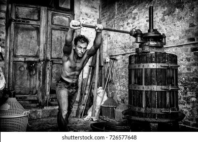 Shirtless winemaker farmer working on a old wine press. Black and white picture