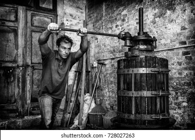 Shirtless winemaker farmer working on a traditional wine press. Black and white picture