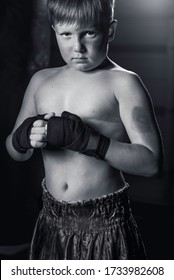 Shirtless young boy wearing boxing hand wraps in gym (black and white)