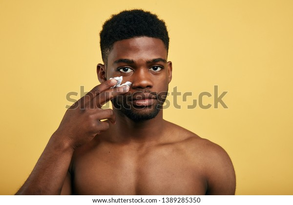 shirtless young brutal african american man applying facial cream on his cheek. close up portrait,men's beauty. skin care