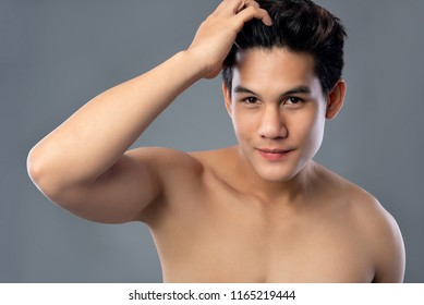 Shirtless young hamdsome attractive Asian man with clean radiant face for male beauty and skin care concepts
