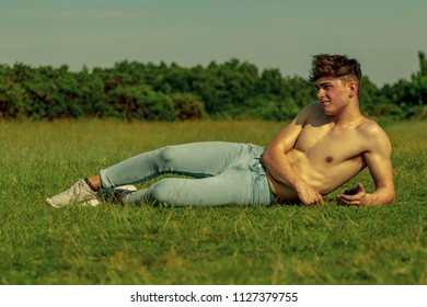 Shirtless young male dult using a mobile phone on a warm summer's day