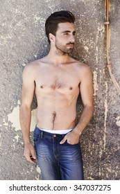 Shirtless young man in jeans looking away
