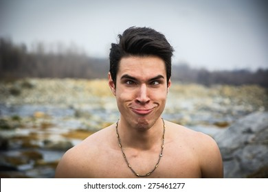 Shirtless young man outdoor doing silly face and stupid expression, looking at camera