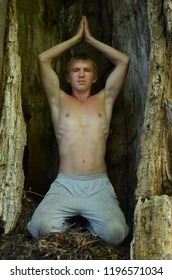 shirtless young man sits and meditates inside the trunk of an old tree, raising his hands above his head in a yoga pose