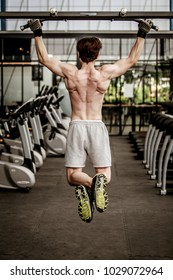 A shirtless young muscular man working out in gym doing exercises with equipment in fitness center.