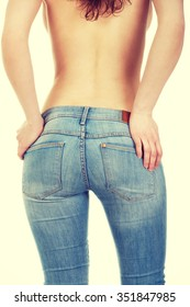 Shirtless young woman alluring in jeans.