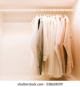 Shirts hanging on rack in built-in cupboard