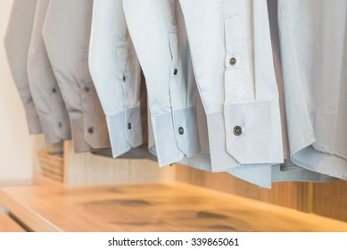 shirts hanging on rack in wooden wardrobe with buttons