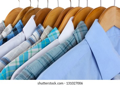Shirts with ties on wooden hangers close-up
