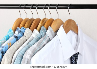Shirts with ties on wooden hangers on light background