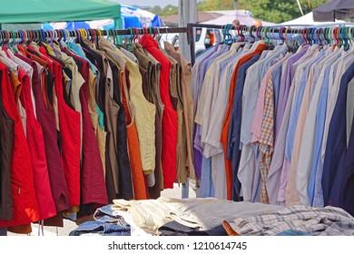 Shirts and vests hanging at clothes rails