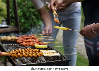 Shish kebab from meat is fried on a brazier in the street in the summer, the man's hand smears meat with oil