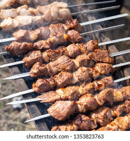 Shish kebab on skewers is fried on a brazier .