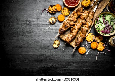 Shish kebab on skewers with grilled vegetables and fresh salad. On the black wooden table.