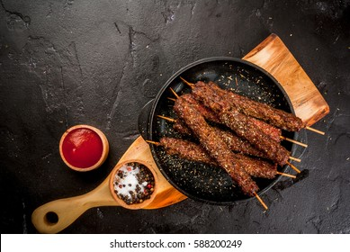 Shish kebab on a stick, from ground beef meat. Lula kebab, traditional Caucasian dish. On the black background of the concrete, on a chopping board, with ketchup, spices and tomatoes copy space above