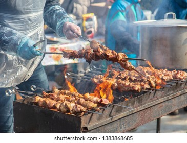 Shish kebab on sticks fried on coals in nature.